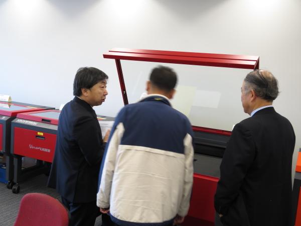 2015年1月ヨコハマシステムズ展示会-ご来場のお客様にレーザー加工機についてご説明している様子